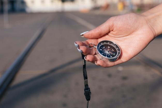 Nahaufnahme der weiblichen hand navigationskompass halten