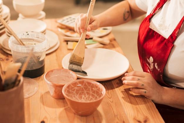 Nahaufnahme der weiblichen handwerkerin die platte mit malerpinsel malend