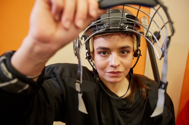 Nahaufnahme der weiblichen hockeyspielerin, die gesichtsschutz öffnet