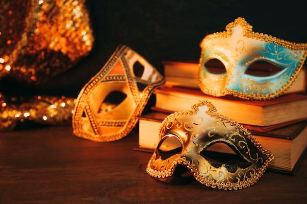 Nahaufnahme der weiblichen karnevalsmaske mit büchern auf hölzernem schreibtisch