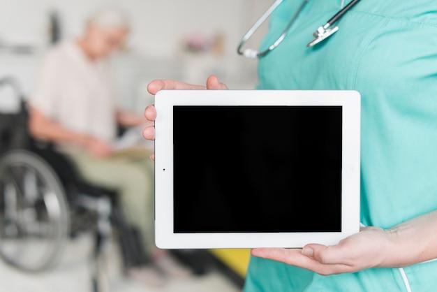 Nahaufnahme der weiblichen krankenschwester leeren bildschirm auf digitaler tablette zeigend