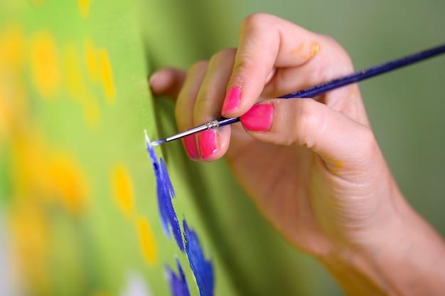 Nahaufnahme der weiblichen künstlerhand, die pinsel hält und ölgemälde zeitgenössischer maler zeichnet, der moderne abstrakte kunstwerke schafft