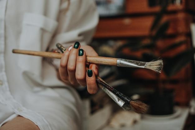 Nahaufnahme der weiblichen künstlerhand, die pinsel in der kunstwerkstatt hält