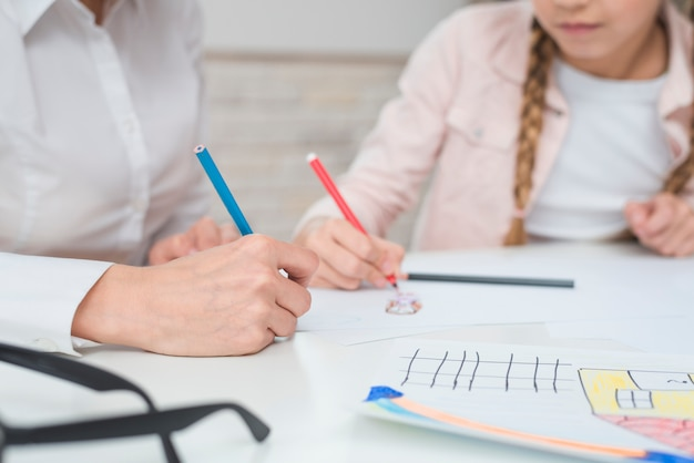 Nahaufnahme der weiblichen psychologezeichnung mit mädchen auf zeichnungspapier über tabelle