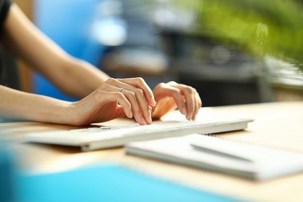 Nahaufnahme der weiblichen tippinformationen auf weißer moderner tastatur. beschäftigter büroangestellter, der monatlichen bericht am computer vorbereitet. papier und silberstift auf dem schreibtisch. technologie- und geschäftskonzept