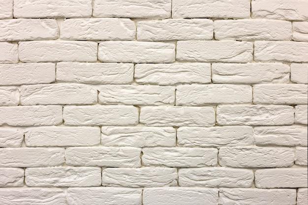 Nahaufnahme der weiß gemalten rehabilitierten festen backsteinmauer. abstrakter kopienraumhintergrund, maurerarbeit-, bau- und maurerarbeitkonzept.