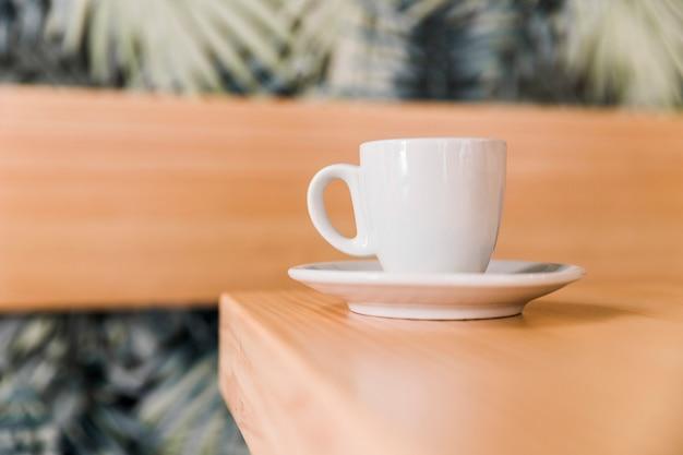Nahaufnahme der weißen kaffeetasse auf hölzernem schreibtisch in cafã?