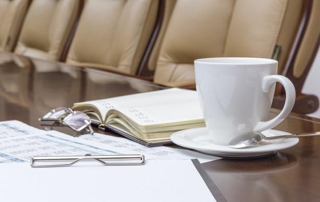 Nahaufnahme der weißen kaffeetasse auf tabelle im leeren unternehmenskonferenzsaal