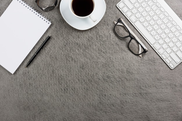 Nahaufnahme der weißen kaffeetasse; tastatur; armbanduhr; stift; spiralblock brillen und tastatur auf dem schreibtisch