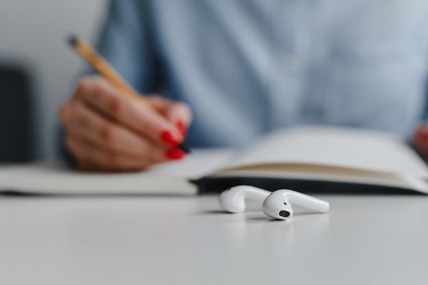 Nahaufnahme der weißen kopfhörer auf dem schreibtisch und der hand der frau mit den roten nägeln, die notizen machen, die blaues hemd am arbeitsplatz tragen.
