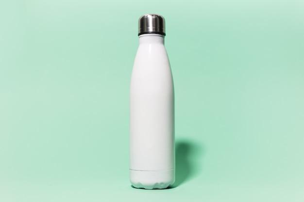 Nahaufnahme der weißen wiederverwendbaren rostfreien thermowasserflasche des stahls, die auf wand der farbe aqua menthe lokalisiert wird. plastik frei.