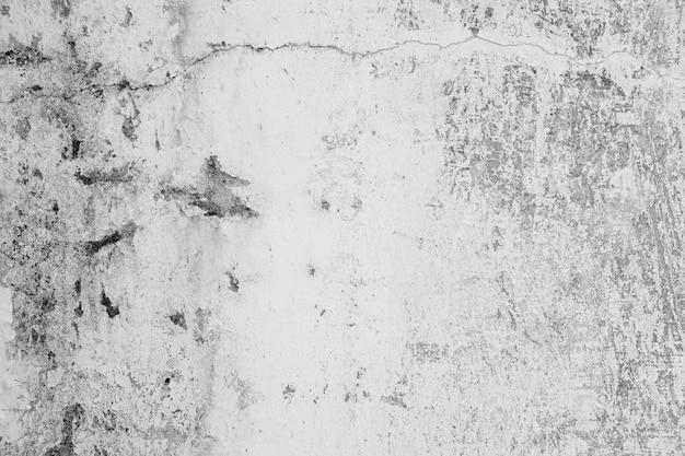 Nahaufnahme der weißzementwand zog der farbe ab, die durch wasser und sonnenlicht verursacht wurde. ziehen sie wand der weißen hausfarbe mit schwarzem fleck ab. schwarzweiss vom beschaffenheitshintergrund.