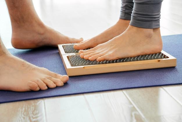 Nahaufnahme der yoga-person, die auf sadhu brett mit scharfen nägeln steht
