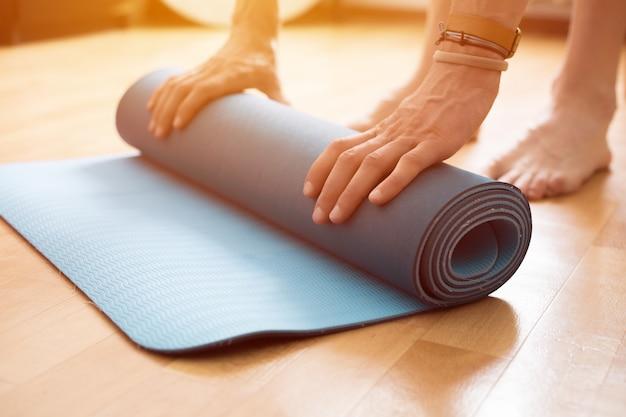 Nahaufnahme der yogamatte in frauenhänden.