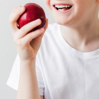 Nahaufnahme der zähne eines gesunden kindes und eines reifen roten apfels. vertikales foto