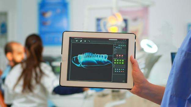 Nahaufnahme der zahnarztassistentin, die tablet mit digitalem zahnärztlichem fingerabdruck des patienten hält, während der arzt mit dem patienten im hintergrund arbeitet und das zahnproblem untersucht, das in einer modernen zahnklinik sitzt.