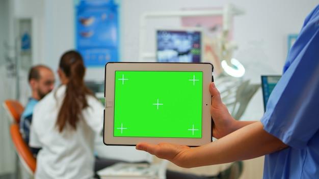 Nahaufnahme der zahnarztkrankenschwester, die tablet mit greenscreen-display in der stomatologischen klinik hält, während der arzt mit dem patienten im hintergrund arbeitet. monitor mit chroma-key-izolate-pc-key-mockup verwenden