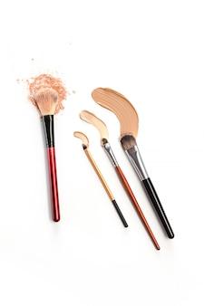 Nahaufnahme der zerquetschten mineralischen schimmerpulvergoldfarbe mit make-up-pinsel