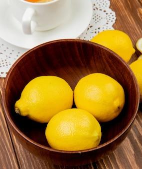 Nahaufnahme der zitronen in der hölzernen schüssel mit tasse tee auf hölzernem hintergrund