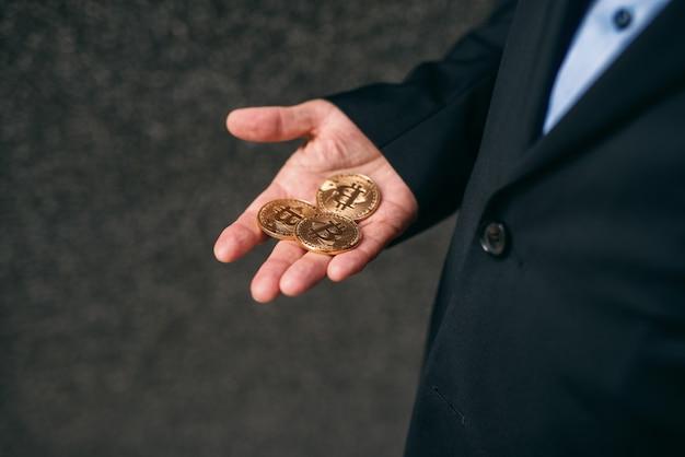 Nahaufnahme des älteren erwachsenen geschäftsmannes, der bitmünzen in der hand hält.
