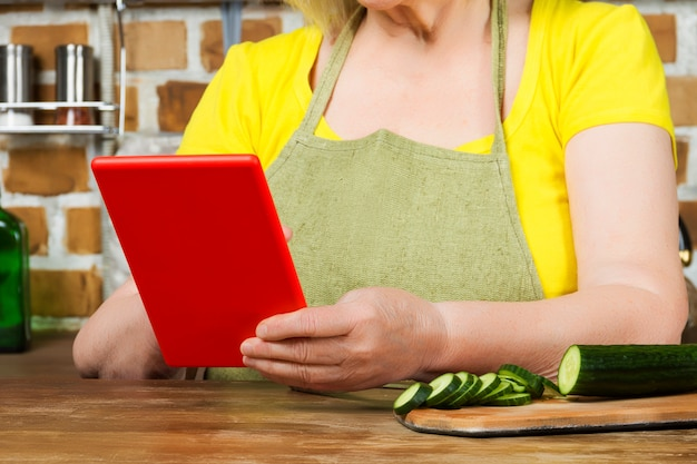 Nahaufnahme des älteren frauenlebensmittelbloggers, der tablette hält