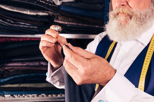 Nahaufnahme des älteren männlichen designers, der das gewebe mit nadel näht