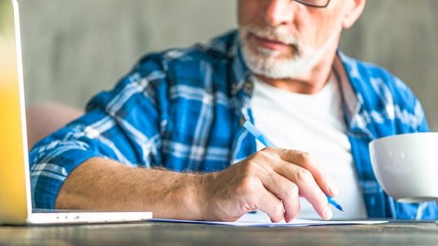 Nahaufnahme des älteren mannes den laptop betrachtend, der anmerkung macht