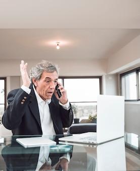 Nahaufnahme des älteren mannes den laptop betrachtend, der auf mobiltelefon im büro spricht