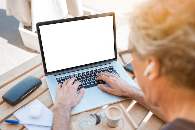 Nahaufnahme des älteren mannes schreibend auf laptop mit weißem leerem bildschirm
