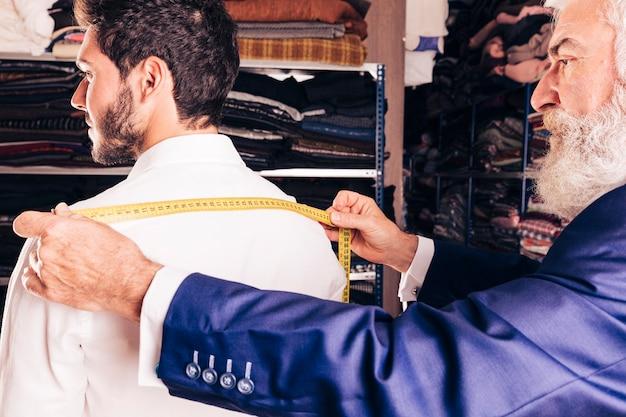 Nahaufnahme des älteren modedesigners maß seines kunden nehmend