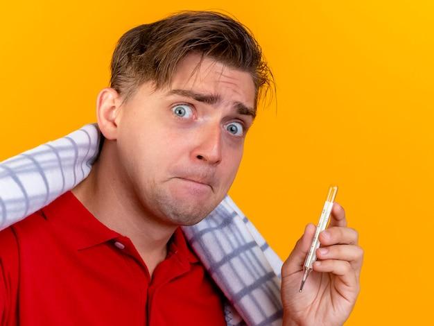 Nahaufnahme des ängstlichen jungen gutaussehenden blonden kranken mannes, der in kariertes haltethermometer eingewickelt auf orange wand eingewickelt wird