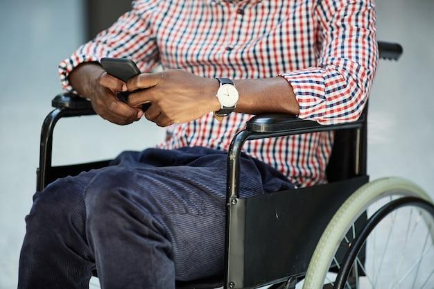 Nahaufnahme des afrikanischen behinderten mannes, der im rollstuhl sitzt und auf seinem handy spielt