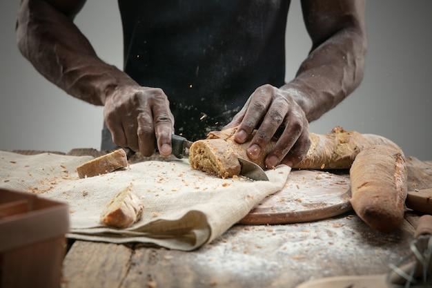 Nahaufnahme des afroamerikaners schneidet frisches brot mit einem küchenmesser