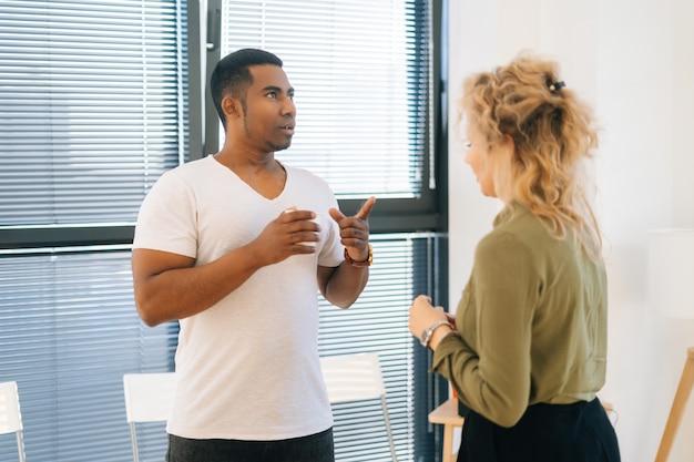 Nahaufnahme des afroamerikanischen mannes, der während der kaffeepause ein gespräch mit einer jungen kollegin führt. zwei multiethnische mitarbeiter genießen eine angenehme kommunikation, diskutieren das projekt auf dem hintergrund des fensters.
