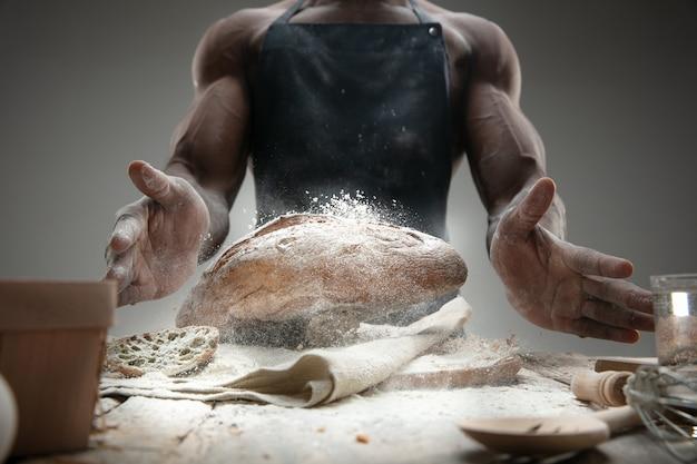 Nahaufnahme des afroamerikanischen mannes kocht frisches müsli, brot, kleie auf holztisch. leckeres essen, ernährung, bastelprodukt. glutenfreie lebensmittel, gesunde lebensweise, biologische und sichere herstellung. handgemacht.
