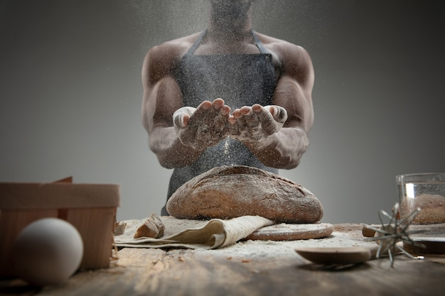Nahaufnahme des afroamerikanischen mannes kocht frisches müsli, brot, kleie auf holztisch. leckeres essen, ernährung, handwerksprodukt. glutenfreie lebensmittel, gesunde lebensweise, biologische und sichere herstellung. handgemacht.