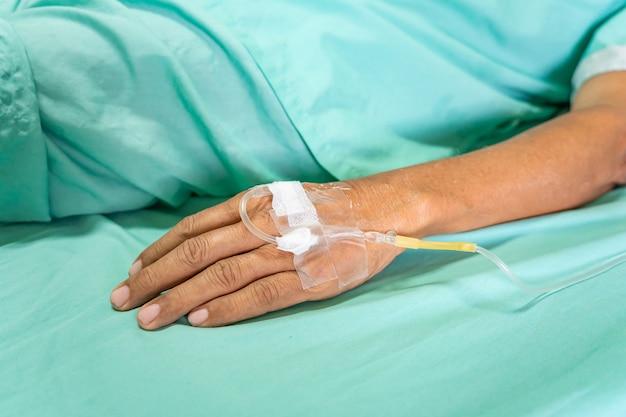 Nahaufnahme des alten mannpatienten mit infusionstropfen im krankenhaus.