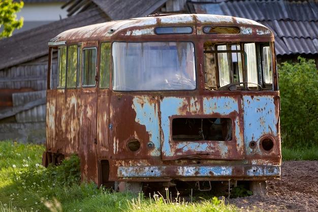Nahaufnahme des alten verlassenen passagierbusses mit zerbrochenen fenstern, die im hohen grünen unkrautigen gras am rand des gepflügten braunen feldes am hellen frühlingstag unter blauem morgenhimmel rosten.