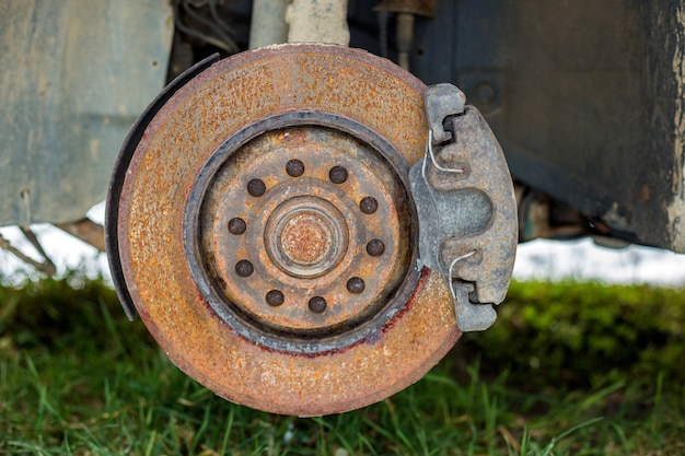 Nahaufnahme des alten verlassenen verlassenen rostigen gebrochenen abfallauto-bremsscheibendetails ohne gummireifen draußen auf dem gebiet.