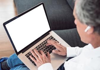 Nahaufnahme des älteren Mannes, der Laptop mit weißem Bildschirm verwendet