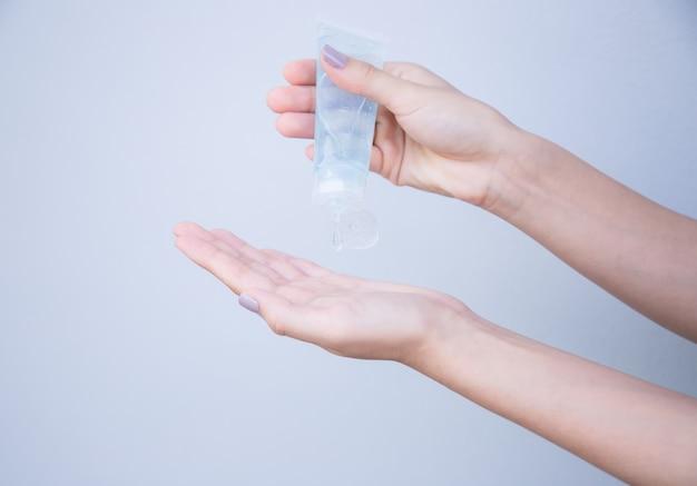 Nahaufnahme des antibakteriellen antiseptischen gels der frau in der hand auf weißem isolat
