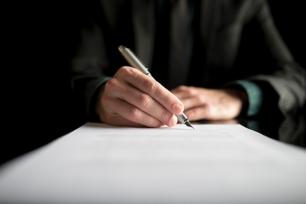 Nahaufnahme des anwalts oder der führungskraft, die einen vertrag unterzeichnet