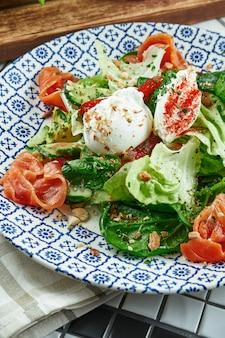 Nahaufnahme des appetitlichen salats mit lachs, spinat, pochiertem ei und ricotta in der schönen blauen keramikplatte auf weißer oberfläche. leckeres essen. flach liegen