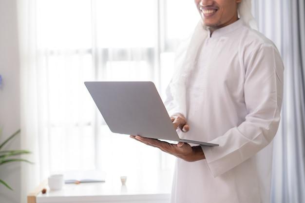 Nahaufnahme des arabischen muslimischen geschäftsmann-stehporträts, das einen laptop gegen das fenster hält