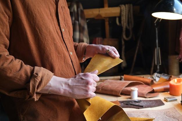 Nahaufnahme des arbeiters, der ledertextilien hält und daraus produkte in der werkstatt herstellt