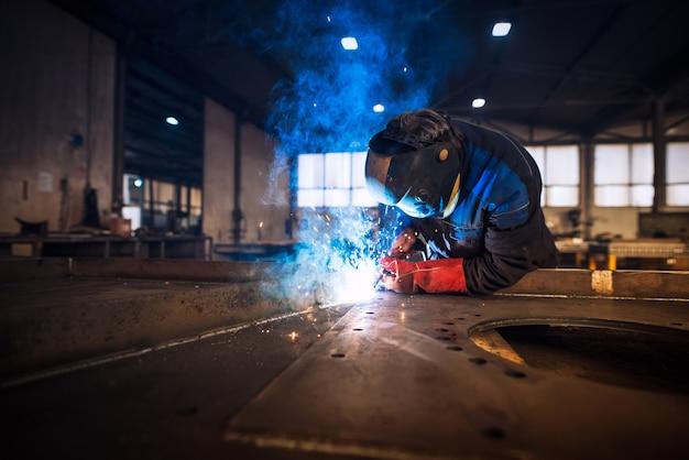 Nahaufnahme des arbeiters, der metallkonstruktion in industrieller werkstatt schweißt
