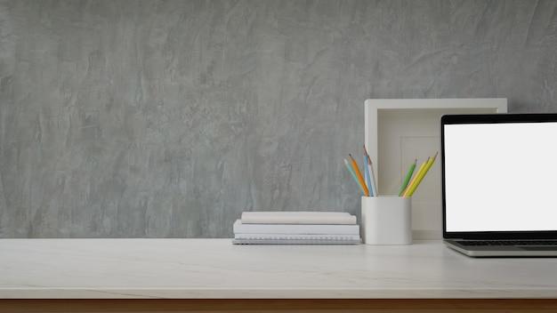 Nahaufnahme des arbeitsbereichs mit laptop, rahmen, büchern, briefpapier und kopierraum