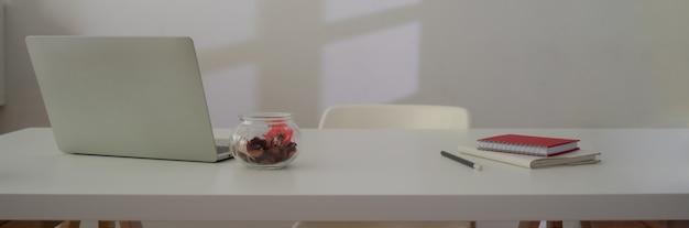 Nahaufnahme des arbeitsbereichs mit laptop, verbrauchsmaterial, dekoration und kopierraum auf weißem tisch