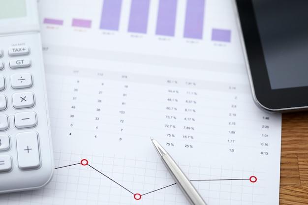 Nahaufnahme des arbeitsplatzes mit geschäftsgraphen und -diagrammen. datenanalyse und taschenrechner auf dem tisch. ergebnisse und einnahmen der unternehmensausgaben. papierkram und bürokonzept