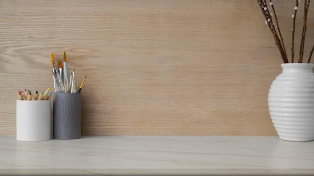 Nahaufnahme des arbeitsplatzes mit kopierraum, malwerkzeugen und keramikvase